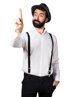 Hipster homme avec barbe touchant sur écran transparent