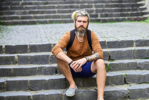 Hipster homme barbu se détendre en plein air. mâle brutal s'asseoir dans les escaliers. mannequin porte des vêtements décontractés. homme mûr avec barbe et moustache. style de salon de coiffure masculin. cheveux teints et sains.