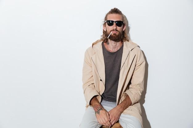 Hipster homme regardant la caméra isolée sur fond de mur.