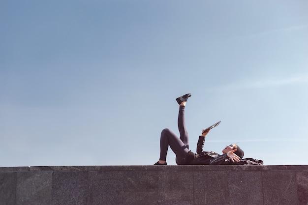 Hipster jeune femme couchée tablette d'utilisation en plein air. fond