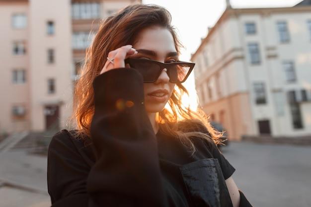 Hipster jeune femme élégante assez européenne dans des lunettes de soleil sombres dans un tshirt élégant avec des lèvres sexy pose près de bâtiments vintage au coucher du soleil