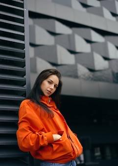 Hipster jeune femme à la mode au repos marchant à l'extérieur dans la ville près d'un grand bâtiment