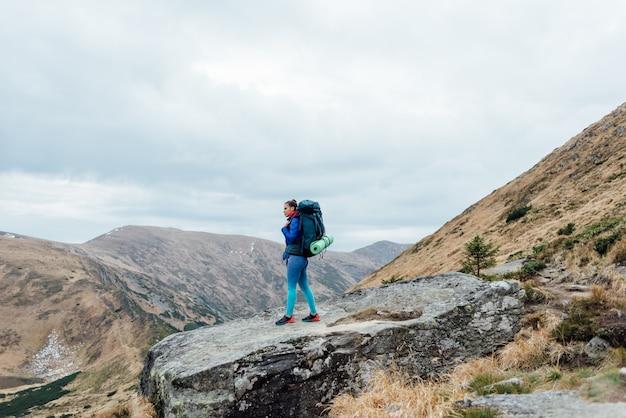Hipster jeune fille avec sac à dos profitant du coucher du soleil sur le sommet de la montagne brumeuse
