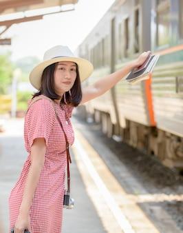 Hipster jeune voyageur attend le train à la gare,