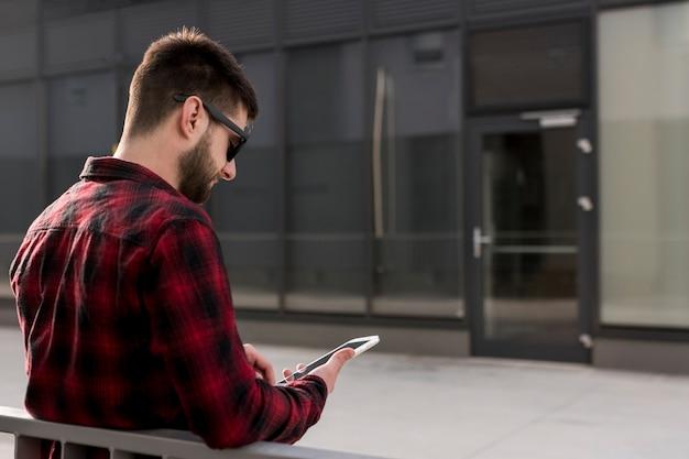 Hipster avec des lunettes de soleil à l'aide de smartphone