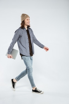 Hipster marchant avec un ordinateur portable