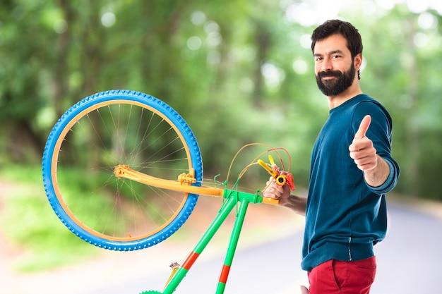 Hipster avec le pouce vers le haut tenant un vélo