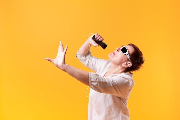 Hipster senior femme danse et chante