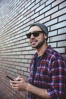 Hipster sms sms application de téléphone dans la rue de la ville sur fond de mur de brique. homme étonnant tenant le smartphone en tenue décontractée intelligente debout. mode de vie professionnel jeune urbain.