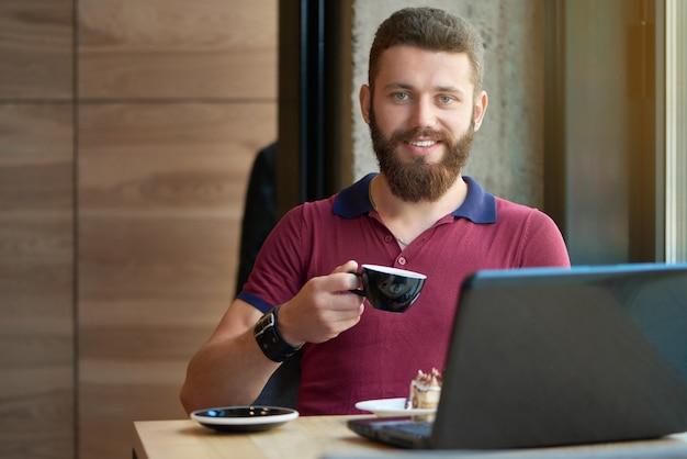 Hipster souriant, gardant la tasse à café, travaillant avec ordinateur portable au café.