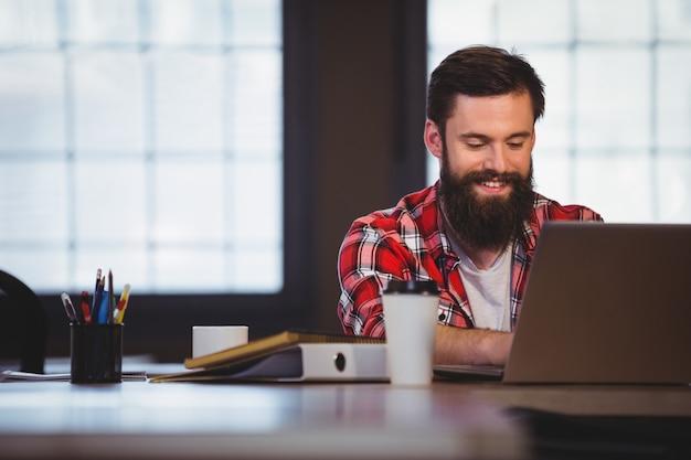 Hipster souriant tout en travaillant sur ordinateur portable