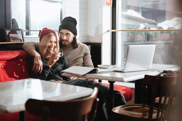 Hipsters assis avec ordinateur portable au café