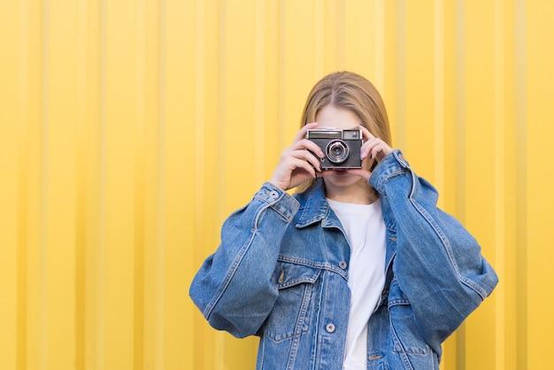 Hipsters femme est sur un mur jaune et prend une photo d'un vieil appareil photo argentique.