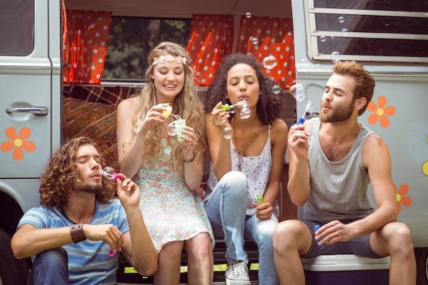 Hipsters soufflant des bulles dans le camping-car