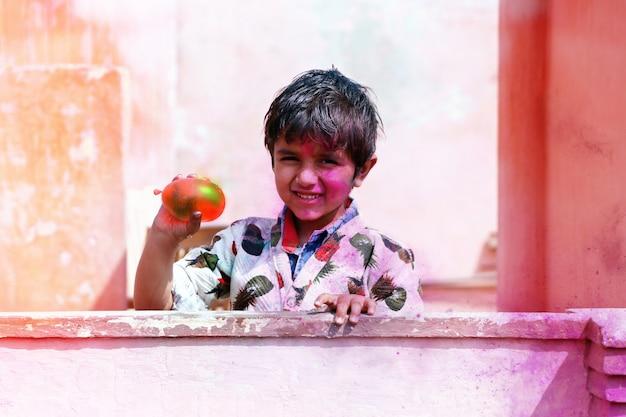 Hisar, haryana, inde mars 2019, petit garçon joue avec les couleurs.& concept de ballons pour le festival indien holi