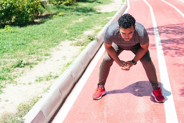 Hispanic man stretching avant sa course