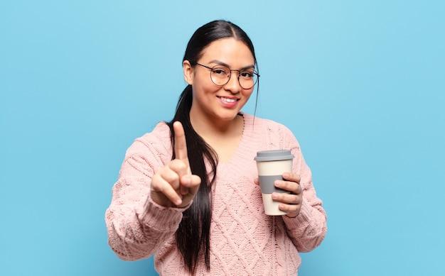 Hispanic woman smiling fièrement et en toute confiance faisant le numéro un pose triomphalement, se sentant comme un leader