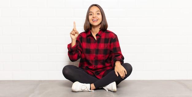 Hispanic woman smiling joyeusement et joyeusement, pointant vers le haut d'une main pour copier l'espace