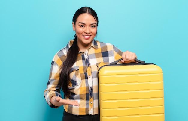 Hispanic woman smiling joyeusement, se sentir heureux et montrant un concept dans l'espace de copie avec la paume de la main