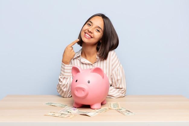 Hispanic woman smiling pointant avec confiance vers son propre large sourire, attitude positive, détendue et satisfaite
