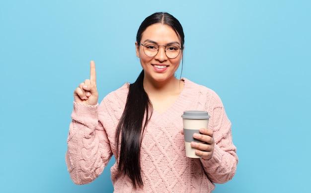 Hispanic woman smiling et à la sympathique, montrant le numéro un ou d'abord avec la main en avant, compte à rebours