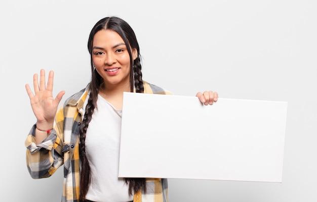 Hispanic woman smiling et à la sympathique, montrant le numéro cinq ou cinquième avec la main en avant, compte à rebours