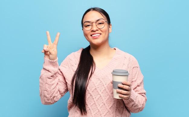 Hispanic woman smiling et à la sympathique, montrant le numéro deux ou seconde avec la main en avant, compte à rebours