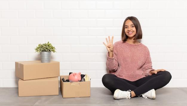 Hispanic woman smiling et à la sympathique, montrant le numéro quatre ou quatrième avec la main en avant, compte à rebours