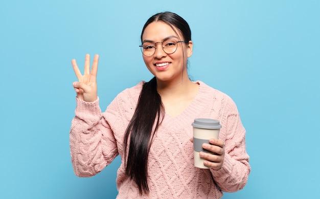 Hispanic woman smiling et à la sympathique, montrant le numéro trois ou troisième avec la main en avant, compte à rebours