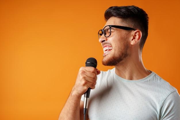 Hispanique jeune bel homme chantant avec joie dans le microphone clsoe up