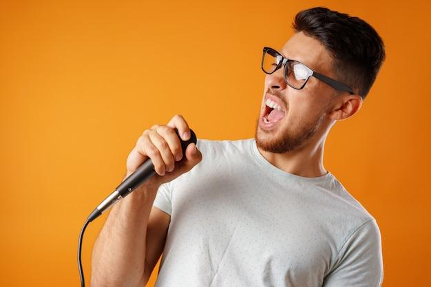 Hispanique jeune bel homme chantant avec joie dans le microphone