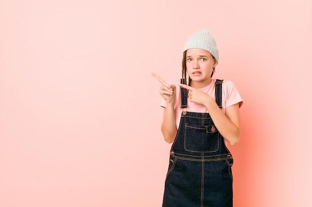 Hispter adolescent femme choquée pointant avec des index vers un espace de copie.