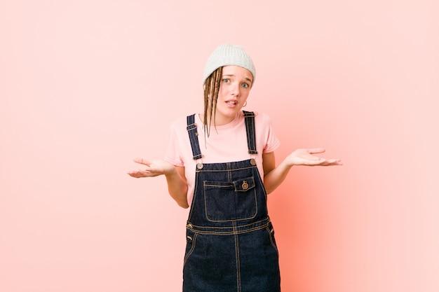 Hispter adolescent femme doutant et haussant les épaules en remettant en question le geste.
