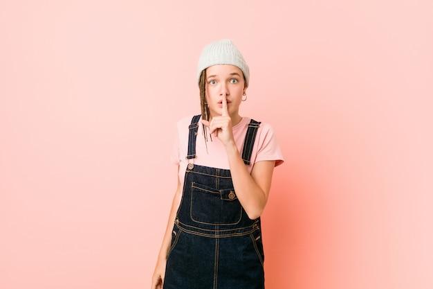 Hispter adolescent femme gardant un secret ou demandant le silence.