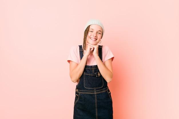 Hispter adolescent femme garde les mains sous le menton, regarde joyeusement de côté.