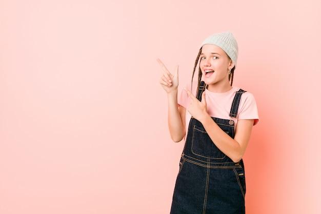 Hispter adolescent femme pointant avec des index vers un espace de copie, exprimant l'excitation et le désir.