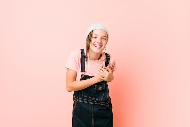 Hispter adolescent femme riant en gardant les mains sur le cœur, concept de bonheur.