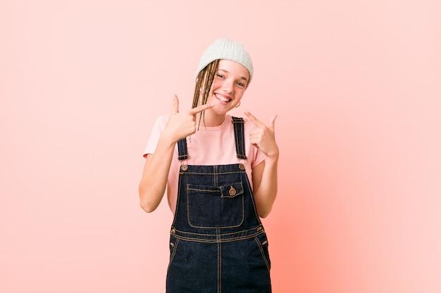 Hispter adolescent femme sourit, pointant les doigts sur la bouche.