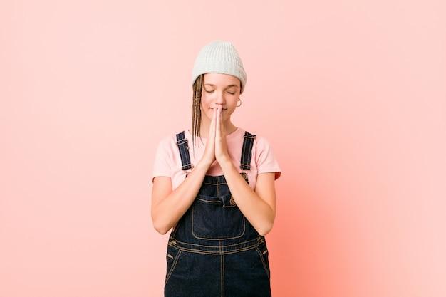 Hispter adolescent femme tenant par la main dans prier près de la bouche, se sent confiant.