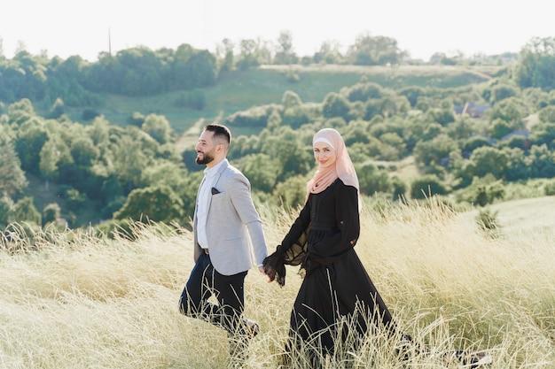 Histoire d'amour musulmane d'un couple mixte. l'homme et la femme sourient et marchent sur les collines verdoyantes.