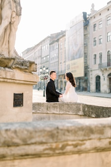 Histoire d'amour ou séance de mariage d'un jeune couple asiatique dans le vieux centre-ville, assis sur la vieille fontaine, matin, heure d'été.