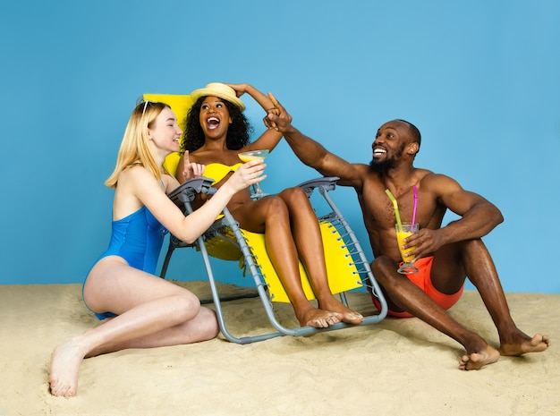 Histoire d'été. heureux jeunes amis se reposer et s'amuser sur l'espace bleu