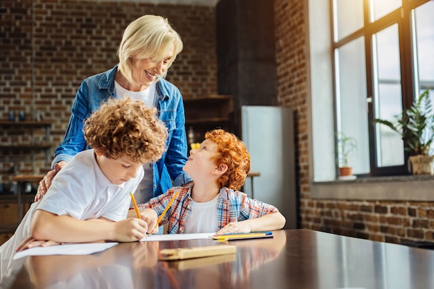 Des histoires réconfortantes. mise au point sélective sur une femme âgée souriant tout en se tenant à côté de ses petits-enfants et en écoutant l'un d'eux lui dire quelque chose d'amusant en dessinant avec des crayons.