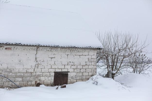 Hiver, ancienne grange délabrée, beaucoup de neige autour.