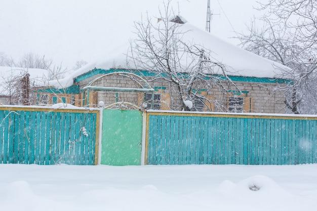 L'hiver au village. vieille clôture branlante délabrée de planches en bois. beaucoup de neige autour