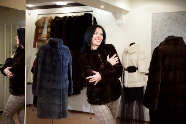 Hiver belle femme en manteau de fourrure. beauté mannequin fille dans un magasin de fourrure.