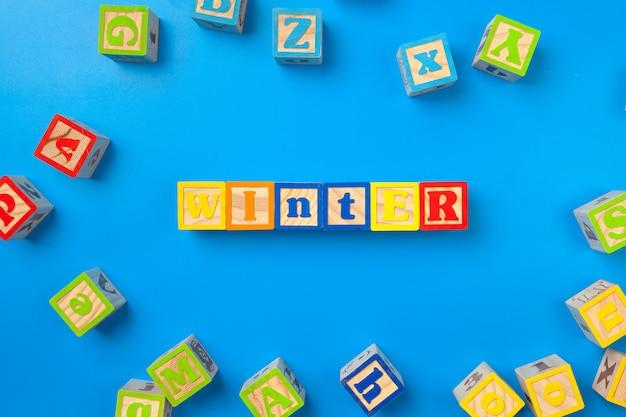 Hiver. blocs d'alphabet coloré en bois sur fond bleu.