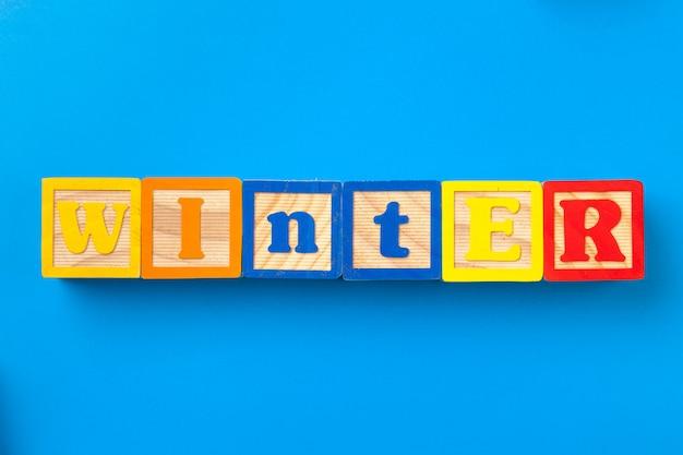 Hiver, blocs en bois alphabet coloré sur bleu, plat poser, vue de dessus,