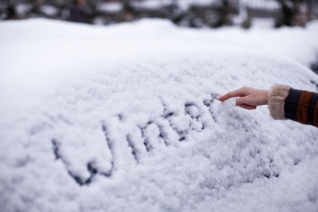 Hiver écrit dans la neige sur la voiture
