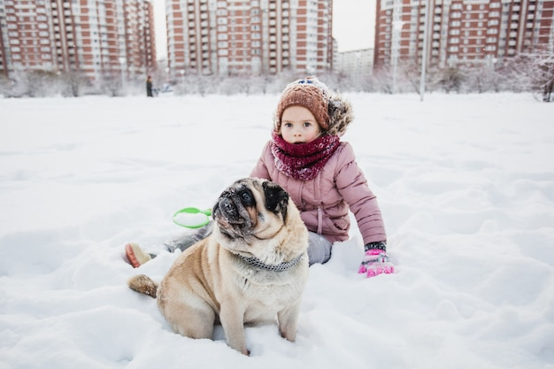 Hiver et une fille avec son chien, neige et jeux dans la neige, promener un animal de compagnie, communiquer avec les animaux